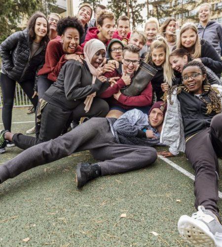 Ryhmä Stadin AO:n opiskelijoita istuskelee urheilukentällä.