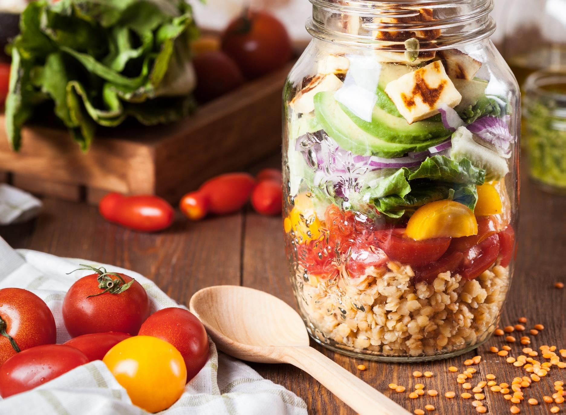 Ruokaa läpinäkyvässä lasipurkissa sekä pöydän päällä.